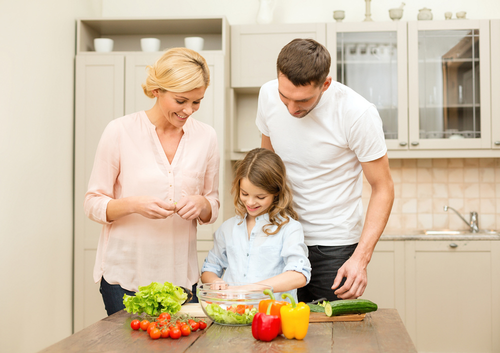 family cutting vegetables in kitchen
